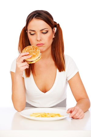 disinclination: portrait of sad woman with burger and deep-fried potatoes