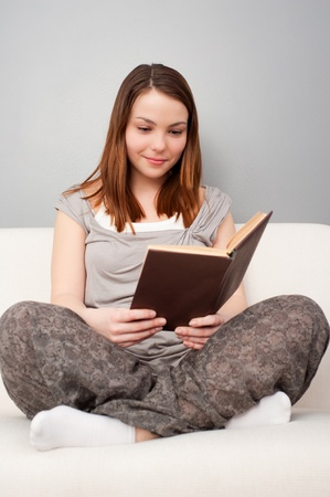 smiley young woman with book sitting on sofa  photo