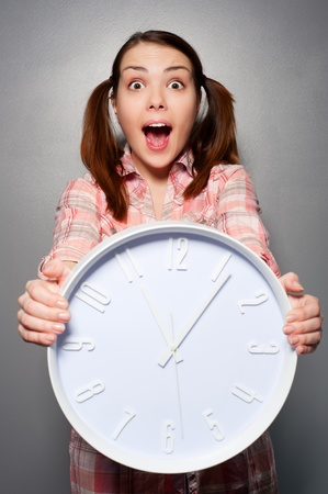 disturbed: portrait of young disturbed woman holding wall clock  Stock Photo