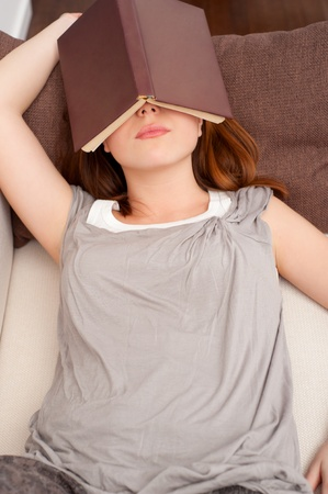 young woman sleeping with book on her face  photo