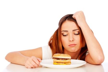 disinclination: portrait of sad woman with burger over white background Stock Photo
