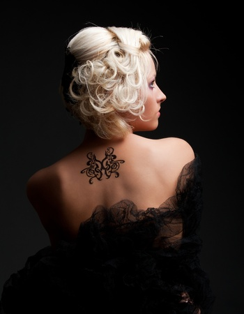 portrait of sexy woman with tattoo on her back  photo