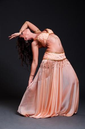 buikdansen: aantrekkelijke vrouw belly dance dansen op zwarte achtergrond