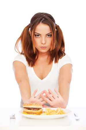 disinclination: portrait of serious woman with burger and deep-fried potatoes. isolated on white
