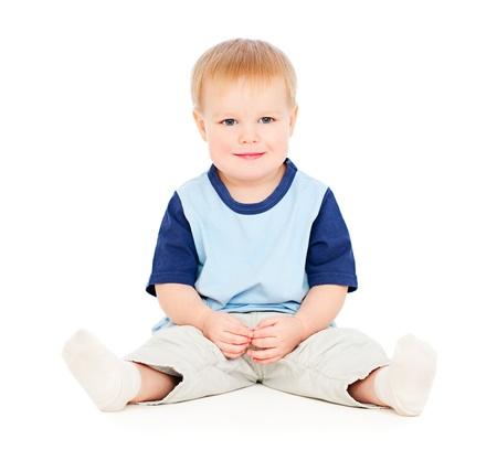 cheerful young boy sitting on floor