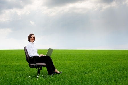 recliner: businesswoman with laptop sitting on recliner over green meadow