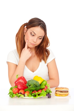 pensive woman choicing burger or vegetables. isolated on white background Stock Photo - 9614877