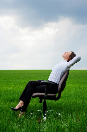 respite: happy businesswoman resting on chair over green meadow