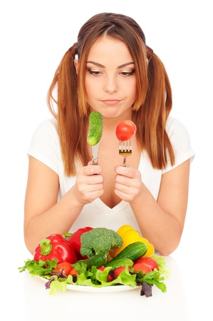 sceptical: sceptical woman looking on fresh vegetables. isolated on white background Stock Photo