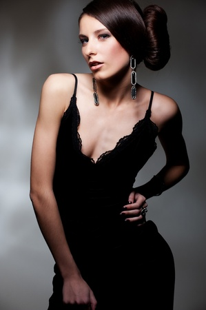attractive brunette in black dress posing over dark background photo