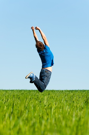 happy man jumping on the green field photo