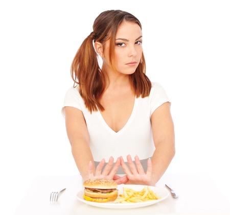 comida chatarra: mujer seria no quiere comer comida chatarra. aisladas sobre fondo blanco  Foto de archivo