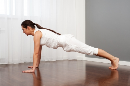 young woman doing yoga exercise in room  photo