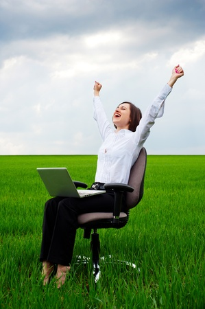 recliner: happy businesswoman with computer sitting on chair over green field  Stock Photo