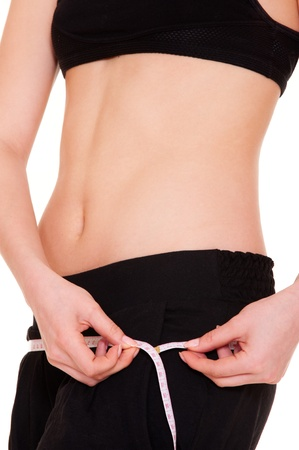 hands on waist: healthy slim woman measuring her hip against white background