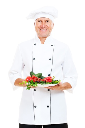 happy chef holding plate with fresh vegetables. isolated on white background  photo