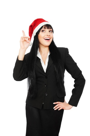 laughing happy businesswoman in santa hat pointing up. isolated on white background photo