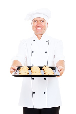 cookie sheet: smiley cook holding baking tray with cookies. isolated on white background