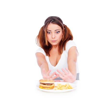 disinclination: young woman dont want to eat junk food. isolated on white background