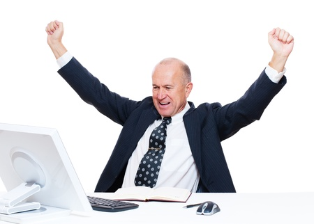 assured: senior happy businessman sitting in workplace and raising hands up