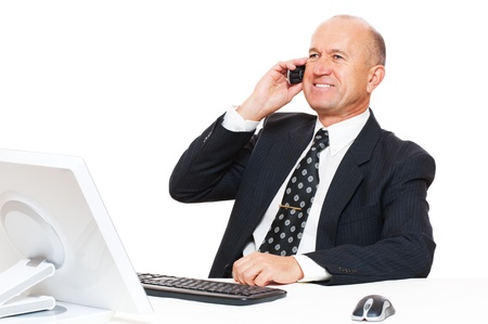 smiley businessman sitting at desk in office and talking on mobile phone photo