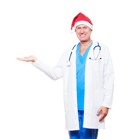 smiley doctor in red santa hat holding something on his palm. isolated on white background Stock Photo - 11103028