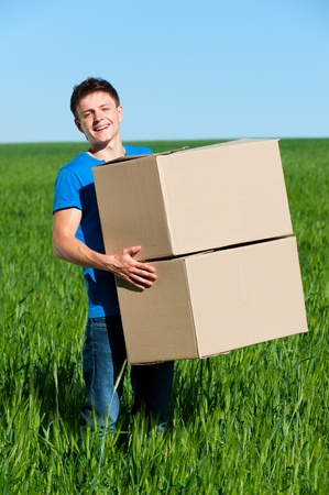 smiley man in blue t-shirt carrying boxes  photo