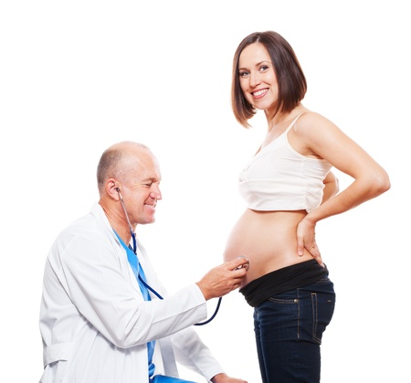 smiley doctor listening pregnant woman's belly. isolated on white background Stock Photo - 11103035