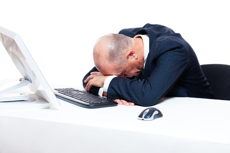 tired businessman sleeping on his workplace over white background photo