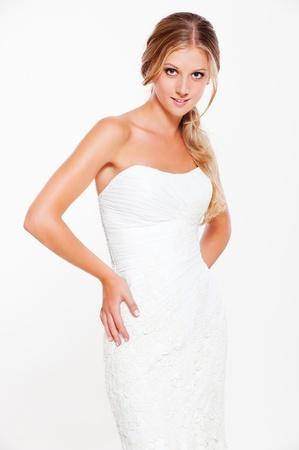 mooie jonge blonde in witte jurk poseren