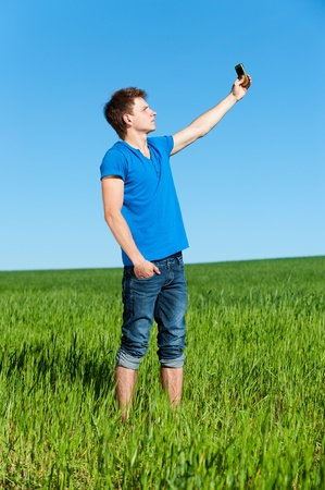 young man taking picture on phone against green grass and blue sky  photo