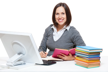 smiley young woman with books sitting on her workplace. isolated on white background