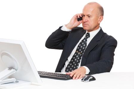 calling: hombre de negocios sentado en el escritorio en la oficina y hablando por tel�fono m�vil Foto de archivo