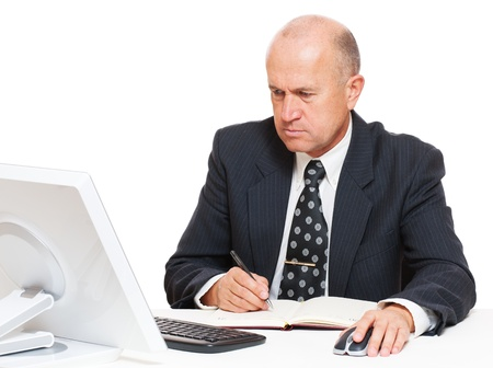 datebook: senior businessman sitting in workplace and writing in datebook