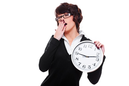 slumberous: drowsy businesswoman holding clock and yawning. isolated on white background