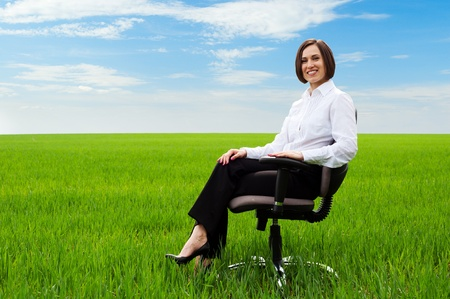 prosperous: happy businesswoman sitting on chair over green field