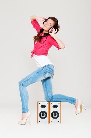 tacones rojos: chica bailando con los auriculares en la cabeza posando cerca de los altavoces Foto de archivo
