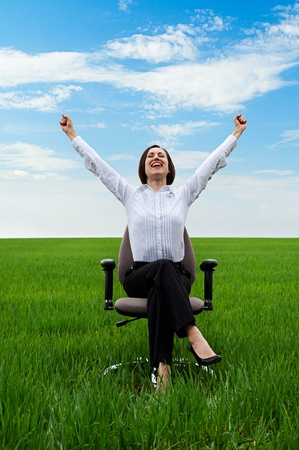 prosperous: happy businesswoman sitting on chair over green meadow  Stock Photo