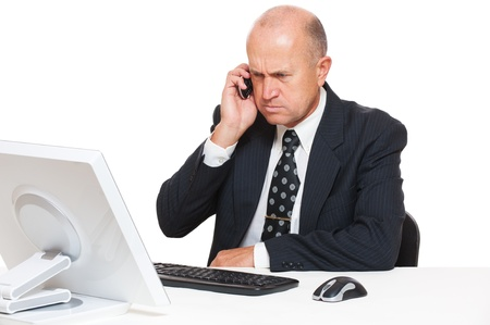 angry businessman: serious businessman sitting at desk in office and talking on mobile phone