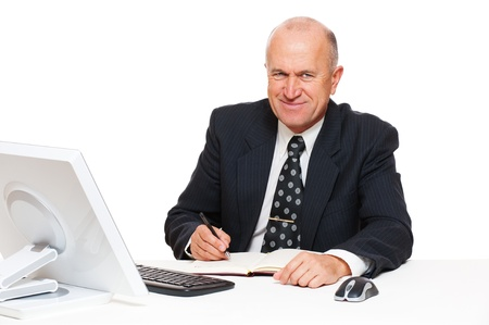 datebook: smiley senior businessman sitting in workplace and writing in datebook