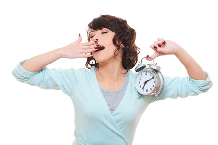 slumberous: tired woman holding alarm clock and yawning. isolated on white background