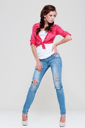 portrait of sexy woman in blue jeans and red shirt posing against grey background  Stock Photo