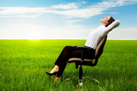 recliner: businesswoman relaxing on chair over green meadow