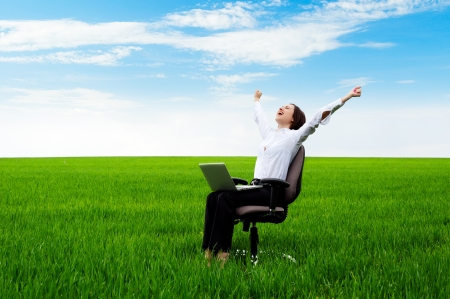 computer model: happy businesswoman with computer sitting on chair over green field  Stock Photo