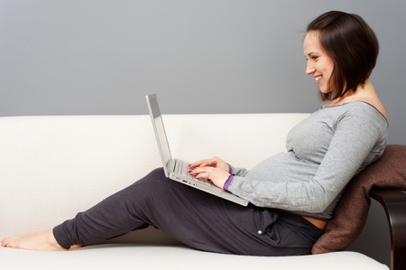 divan sofa: cheerful pregnant woman with laptop sitting on sofa