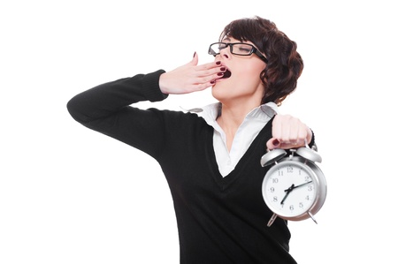 slumberous: drowsy businesswoman holding alarm clock and yawning. isolated on white background  Stock Photo