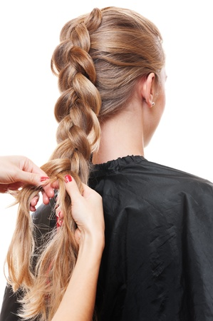 hairdresser doing up ones hair in a plait. isolated on white background