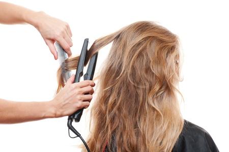 supercharger: hairdresser straightening hair over white background