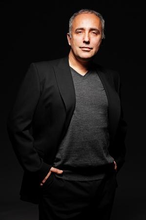 one mid adult male: portrait of handsome senior businessman over dark background
