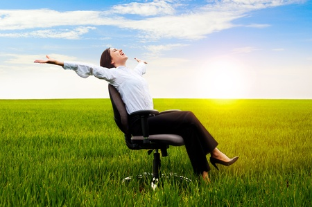 recliner: happy businesswoman resting on chair over green meadow